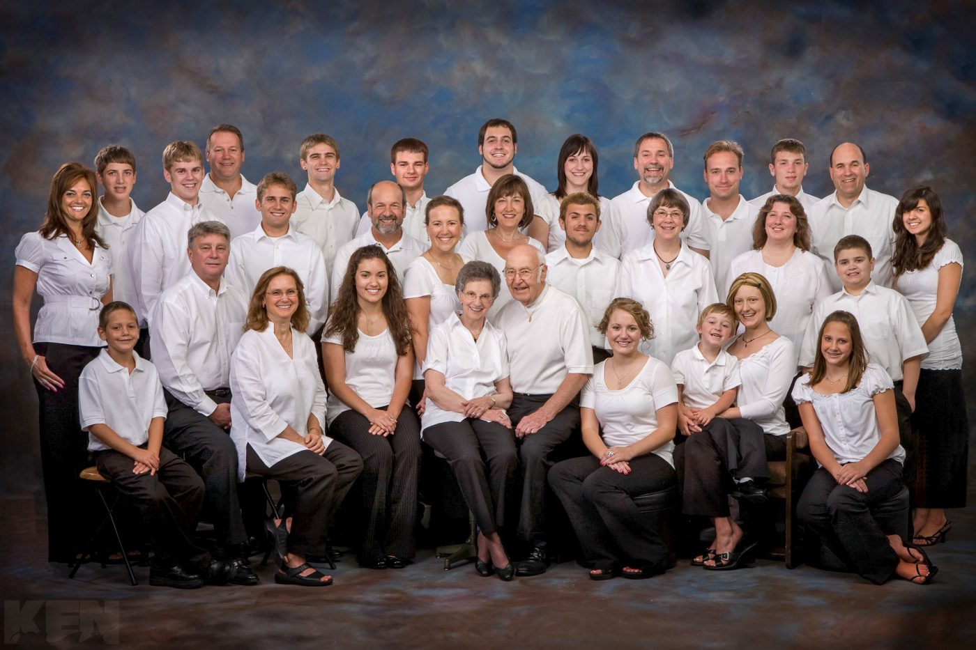 A family of 3 generations and over 30 people poses comfortably wearing white shirts.