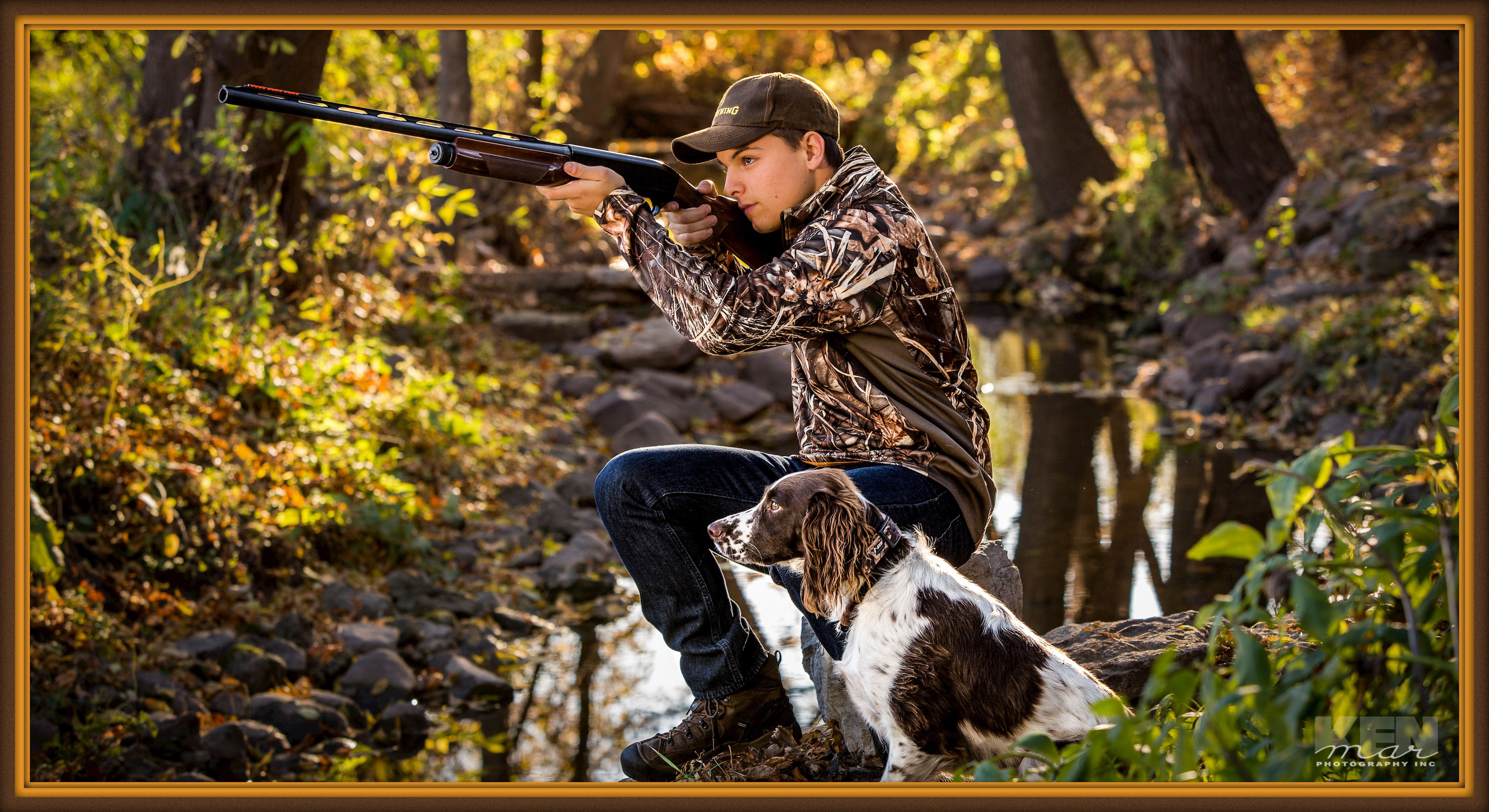 Young man posed outdoors by stream with hunting gun and dog